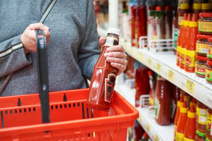 A shopper puts a bottle of ketchup into a grocery basket.