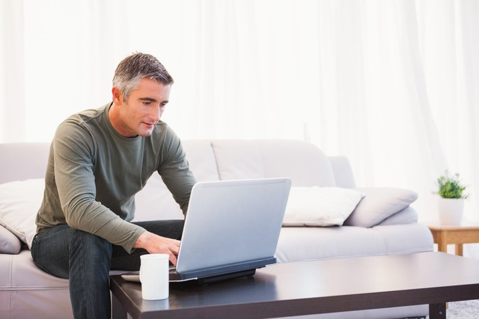 Man sitting on couch, typing on laptop on coffee table in front of him