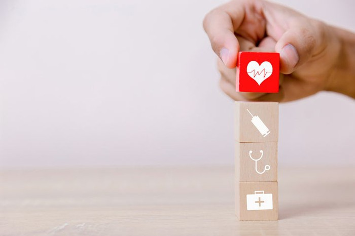 A hand placing a red wooden block with a heart on its face atop several blocks with medical icons on them.