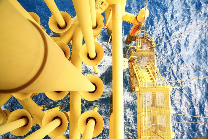Yellow pipes descend into the water at an offshore oil platform