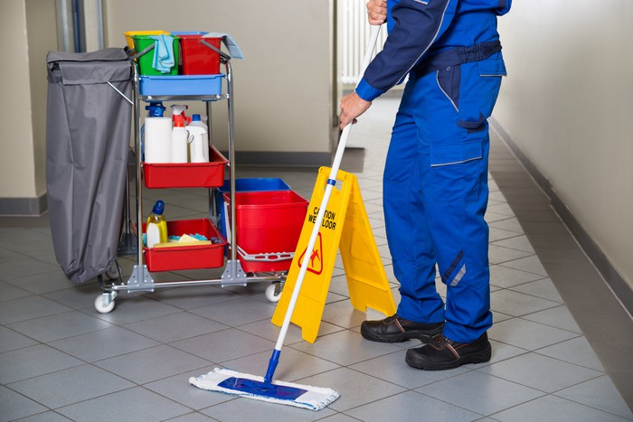 A custodian in a blue uniform mops an office corridor with his supplies cart nearby.