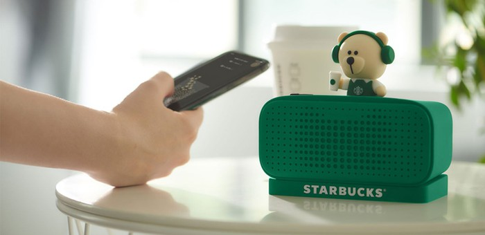 A speaker says Starbucks while a person holds a remote control.