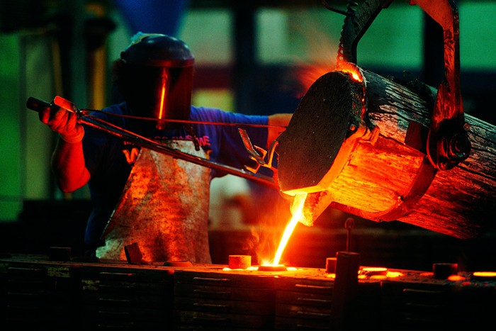 Ironworker pouring molten steel from a bucket