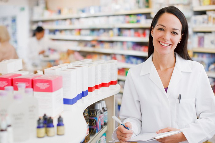Smiling pharmacist holds a pad and paper while standing next to a shelf filled with medicines.