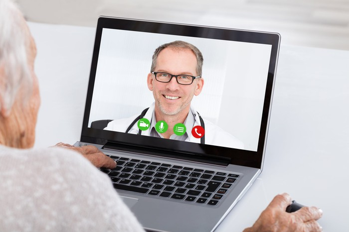 A senior talks with a doctor on a computer using a virtual health service.