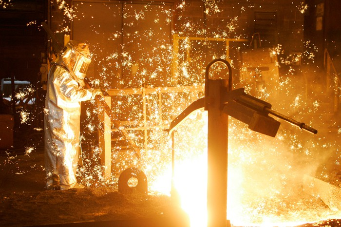 Sparks and a man in protective clothing as US Steel shares drop today in the stock market.