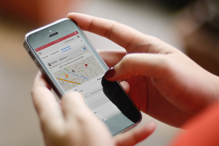 A woman's hands holding a smartphone while looking at the Grubhub mobile app.