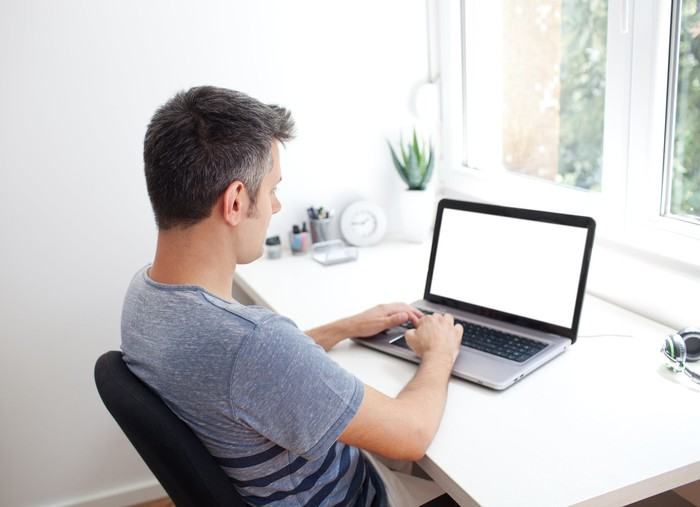 A man in a T-shirt works on a laptop, which is on a table near a window.