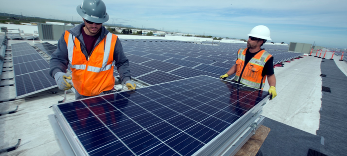 Workers installing solar panels on the roof of an Amazon warehouse