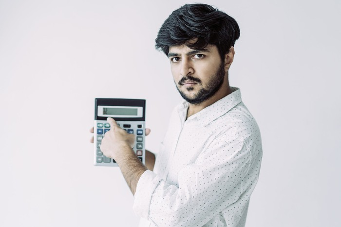 An unhappy young man with a beard points to a calculator as if showing the numbers to you.