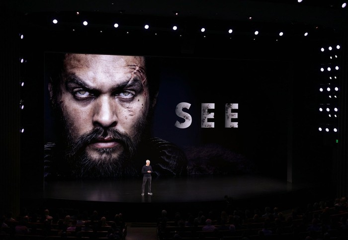 Tim Cook stands on a dark stage with a large image of actor Jason Momoa and the word See on a screen behind Cook.