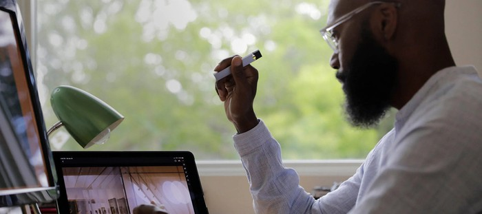 A man holds a Juul e-cigarette as he works in front of a laptop.