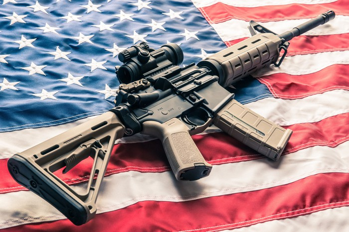 An AR-style rifle on top of an American flag
