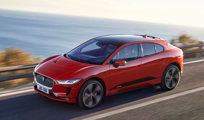 A red Jaguar I-Pace, a sleek electric crossover SUV, on a waterfront road.