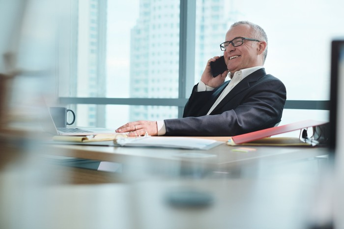 Smiling older man in business suit talking on phone