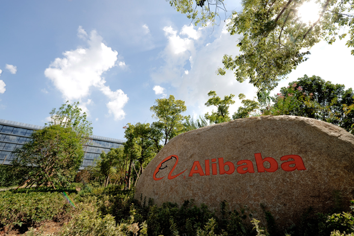Alibaba headquarters with company symbol out front of Alibaba building.