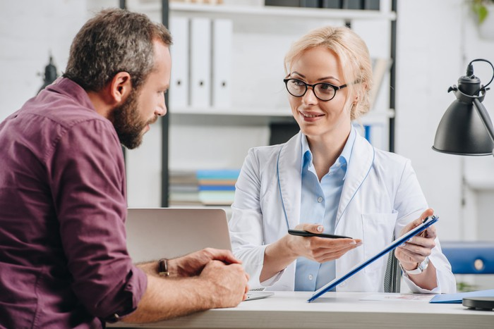 Woman in white coat gesturing toward clipboard while man looks on