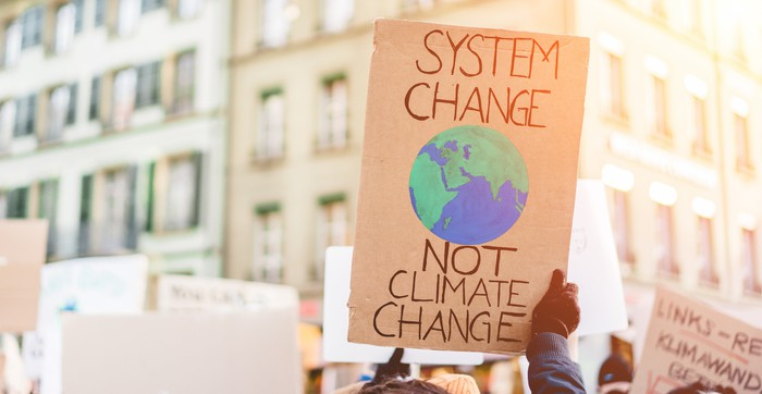 A protester holds up a sign reading System Change, Not Climate Change