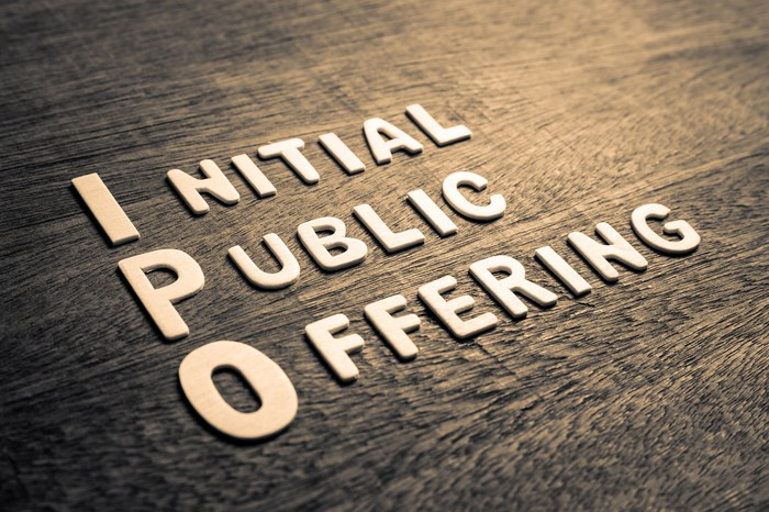The words initial public offering with capitalized I, P, and O printed on a manufactured wood floor.