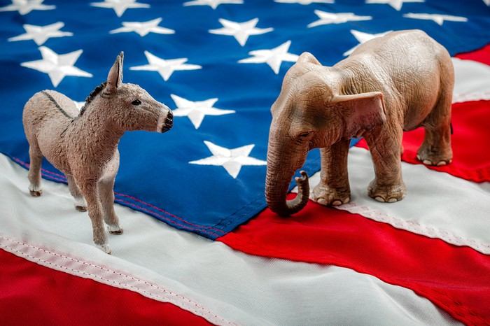 A Democrat donkey and Republican elephant facing off atop an American flag.