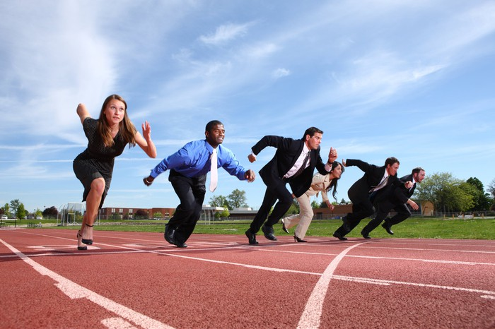 People in business attire taking off running on a track.