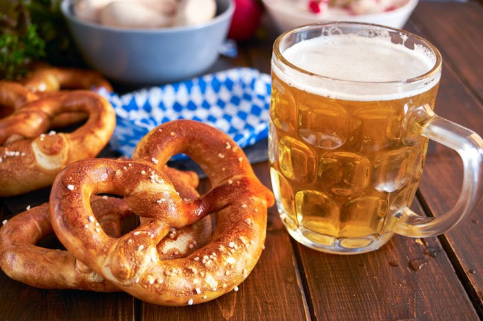 A glass mug of beer and three large soft pretzels on a wood table with other foods and a blue-and-white checked napkin in the background.