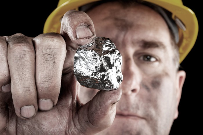 A miner holding up a shiny piece of metal.