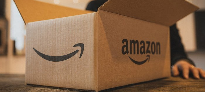 An open Amazon box with part of a person's hand visible next to it.