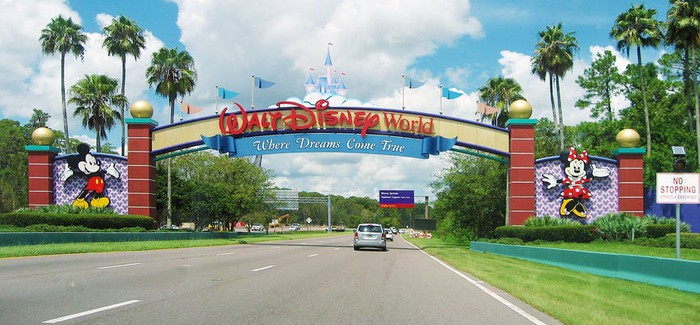 A street entrance to Disney World in Florida showing an overhead sign reading Walt Disney World with images of Mickey and Minnie Mouse.