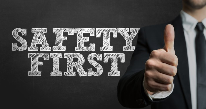 The words safety first with a man giving a thumbs up sign in the background