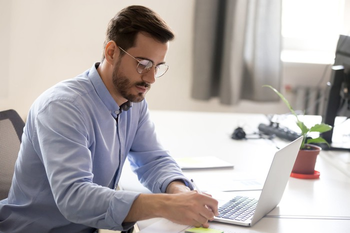 Man sitting at desk with open laptop, taking notes