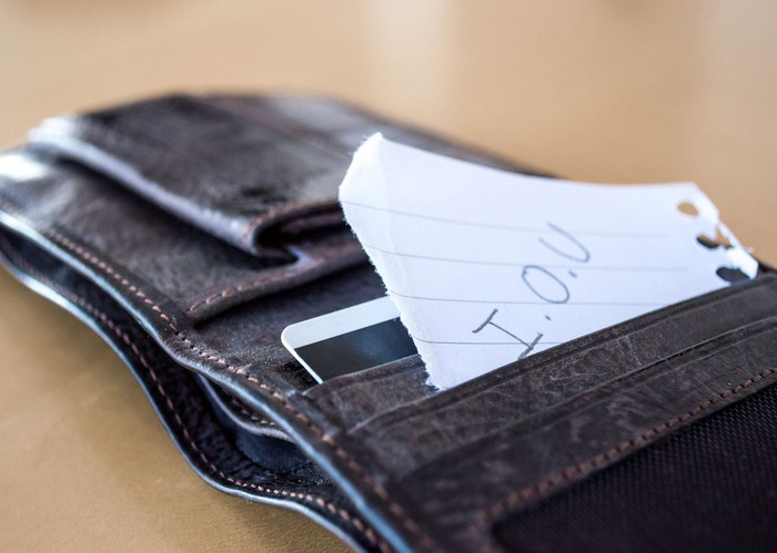 A wallet with an IOU paper sticking out