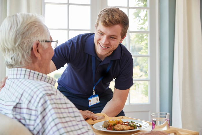 Young man in scrubs leaning over toward older man with meal in front of him
