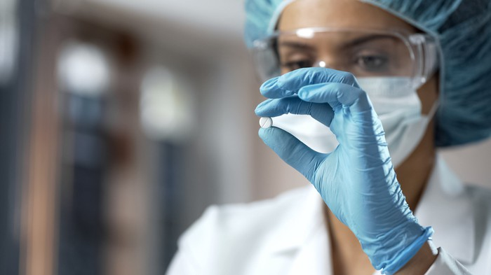 A female chemist inspecting a small white pill.