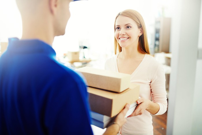 A woman receives multiple packages from a deliveryman