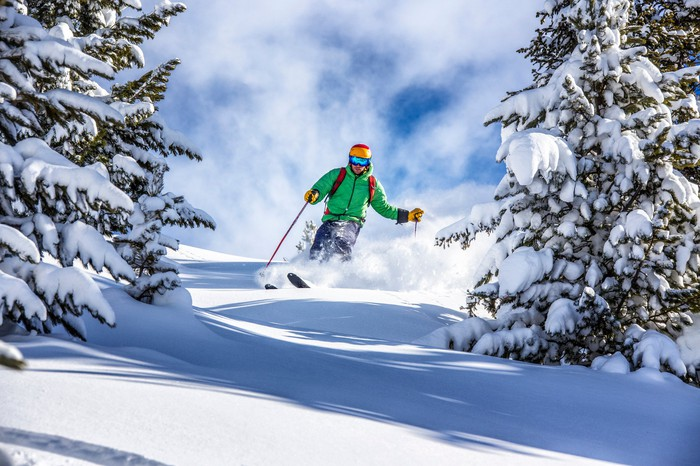 A man skiing down a mountain slope between snow-covered fir trees.