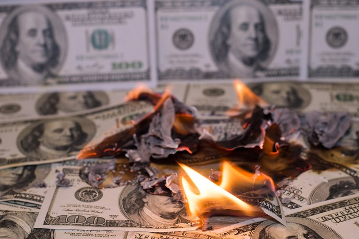 A small pile of one hundred dollar bills on fire, with one hundred dollar bills used as wallpaper in the background.