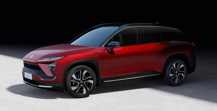 A red NIO ES6, a sleek battery-electric compact crossover SUV.
