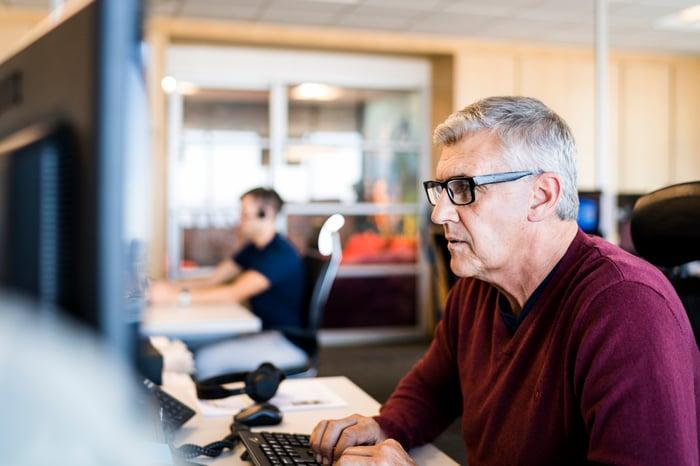 Older man at computer typing on keyboard.