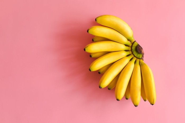 Ripe bunch of bananas on a pink background.