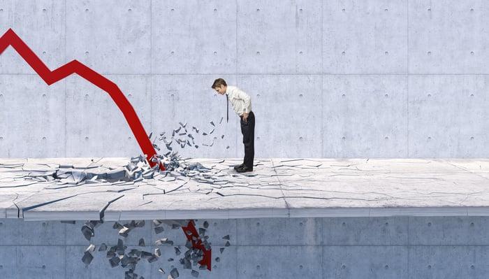 Businessman stares at stock arrow crashing through the floor