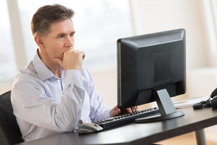 Man with a serious expression looking at computer screen.