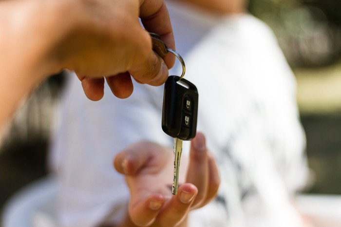 One person passes car keys to another.