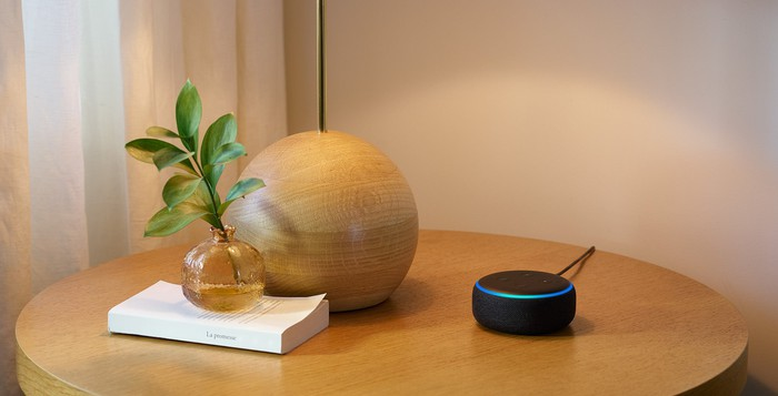 Echo Dot on a table next to a lamp and a book