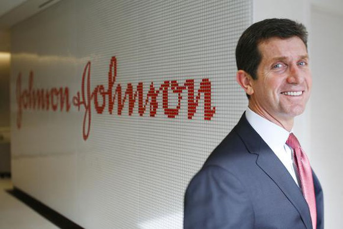 Johnson & Johnson CEO Alex Gorsky smiling in front of his company's corporate logo.
