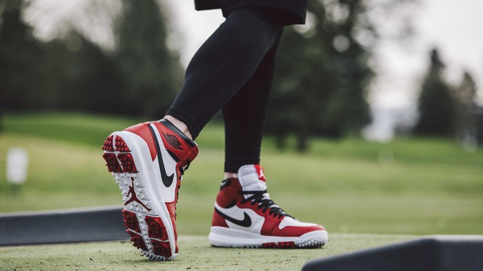 Red, black, and white Nike Air Jordan golf shoes.