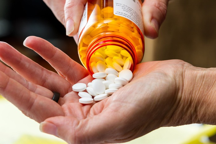 Prescription bottle pouring pills into a hand