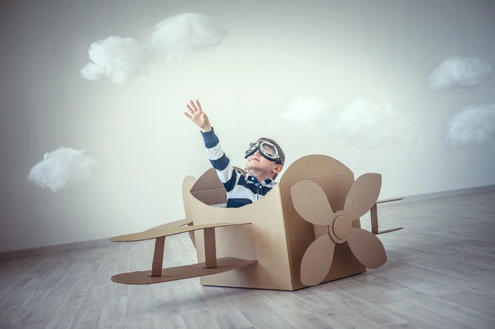 A kid playing inside an airplane made from cardboard boxes.