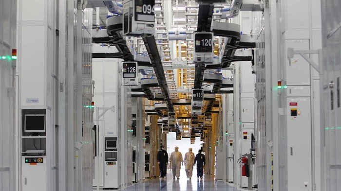 People wearing white lab suits walking through a semiconductor factory.