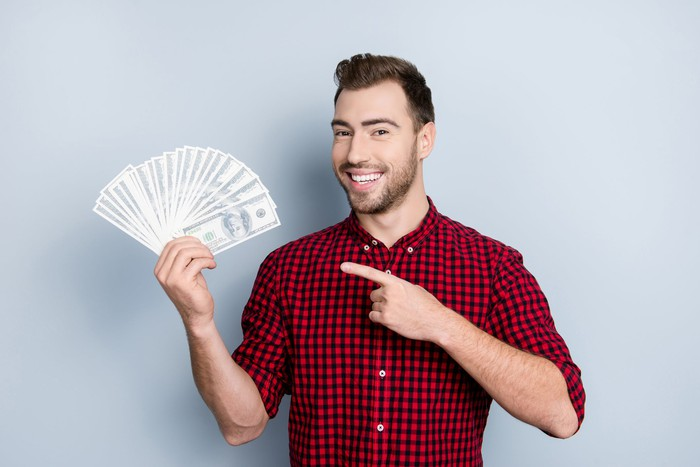 Smiling man fanning out a bunch of hundred-dollar bills and pointing toward them.
